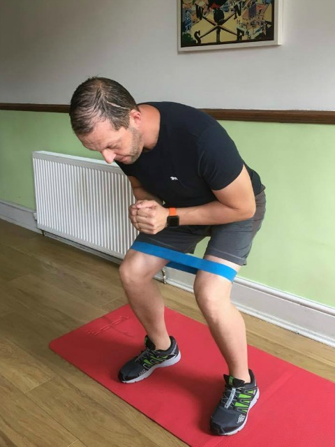 squat using a small loop resistance band